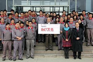 杭州経済技術開発区から授与された奨励金847万元の賞状を掲げる杭州優科豪馬輪胎の持永義登総経理と従業員。